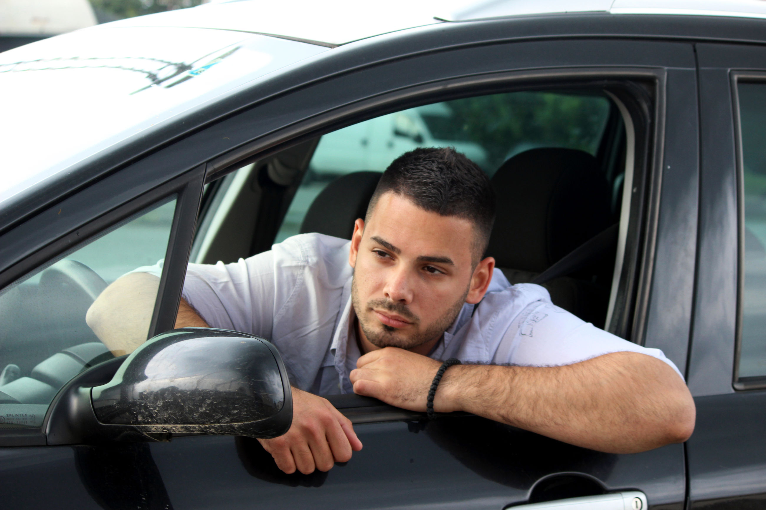 PORTRAIT OF YOUNG MAN SITTING BY CAR