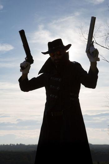 Man in long coat holding guns against sky