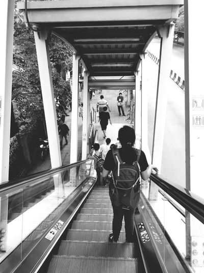 High angle view of woman standing on escalator by road
