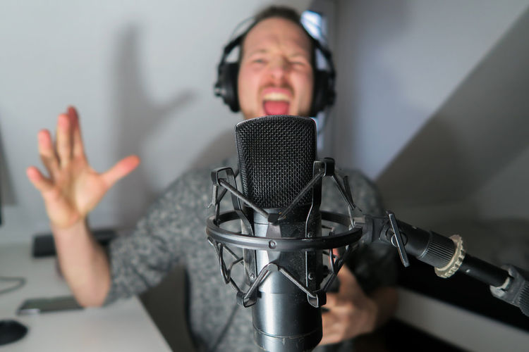 Young male podcaster, youtuber with condenser microphone Microphone Input Device Front View One Person Indoors  Communication Technology Gesturing Music Adult Headshot Arts Culture And Entertainment Human Body Part Mouth Mouth Open Talking Portrait Mature Adult Listening Human Arm