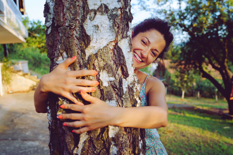 Young woman smiling while standing on tree trunk