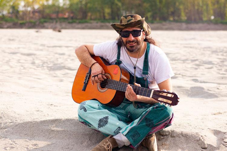 Man playing guitar on beach