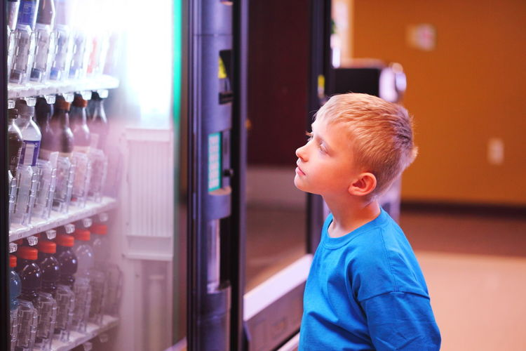 Boy standing and looking at vending machine in store