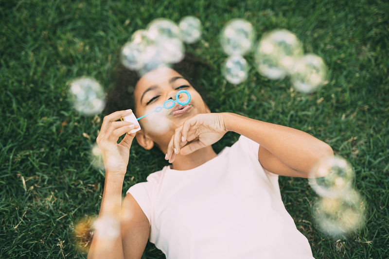 African American Bubbles Fun Grass Holidays Lying Brunette Cheerful Childhood Cute Day Girl Joy Kid One Person Park Selective Focus