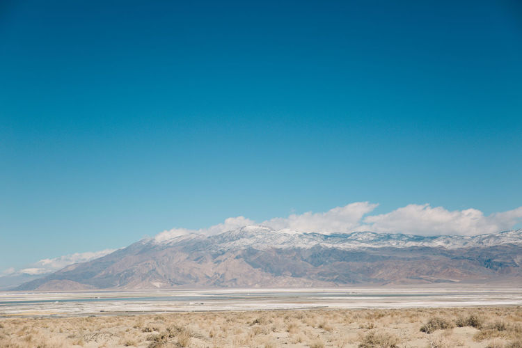 Scenic view of death valley desert against blue sky