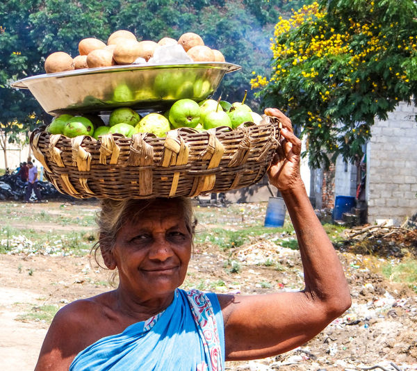 Portrait of smiling senior woman carrying fruits in basket in city
