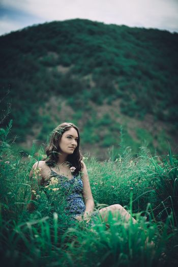 Young woman looking away while sitting on grassy field