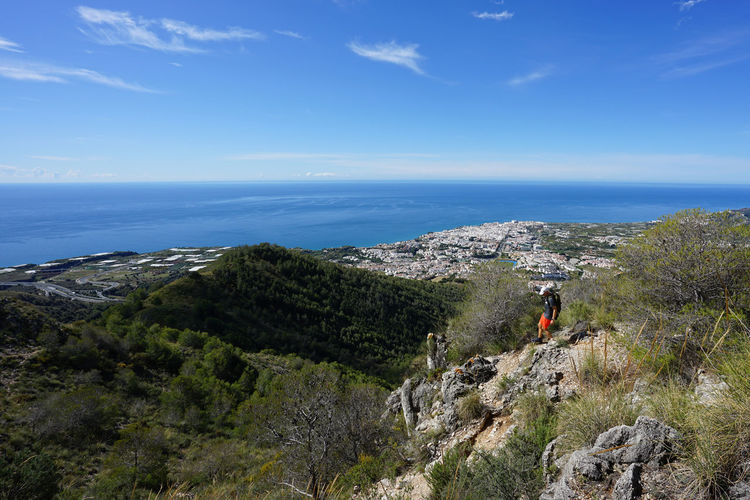 Man hiking on mountain against sea
