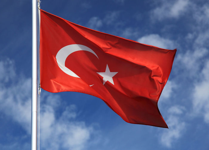 Low angle view of turkish flag waving against sky
