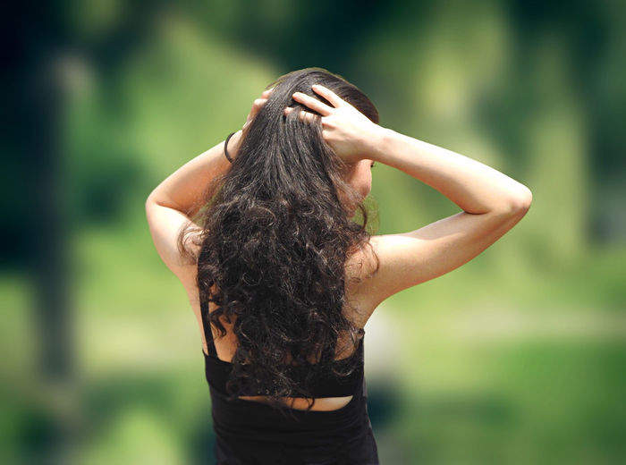 Rear view of woman standing with hands in hair