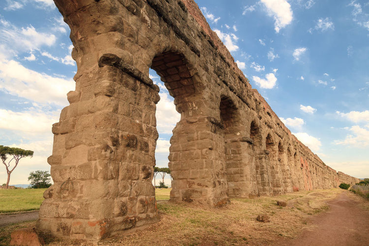 Low angle view of ancient roman aqueduct against sky
