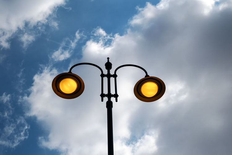 city lit light pole on day with cloudy sky City Lit Light Pole On Day With Cloudy Sky Cloud - Sky Sky Lighting Equipment Street Light Street Low Angle View No People Nature Electricity  Light Outdoors Pole Illuminated Day Yellow Electric Light Technology Sign Light - Natural Phenomenon Communication Electric Lamp Electrical Equipment