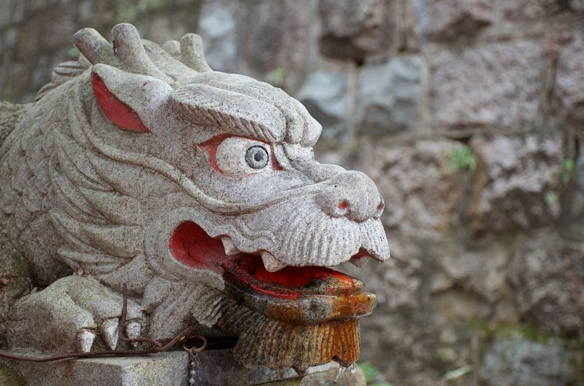 A dragon statue watches over a shrine Animal Representation Art And Craft Focus On Foreground Close-up Dragon Mouth Open Japan Travel Stone Statue Asian Art Cultural Artifact Shrine No People Mythical Creature