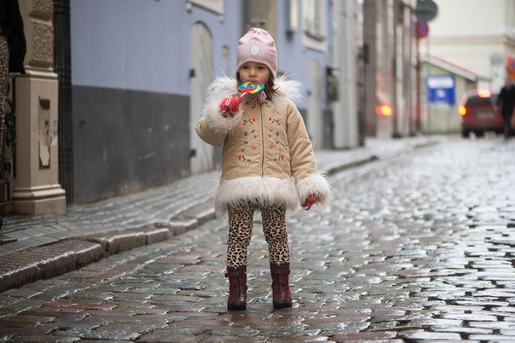 Girl eating lollipop while standing on street in city