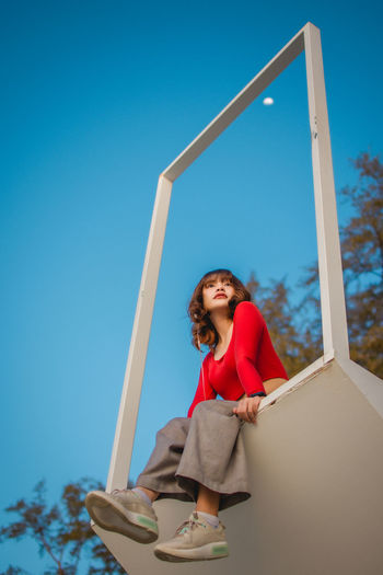 Low angle view of young woman holding umbrella against blue sky