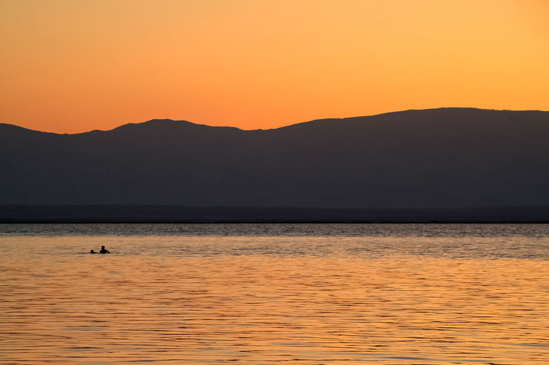 Person floating on surface of Dead Sea, Israel, where high salt content causes you to float naturally Dead Sea  Israel Sunrise Low Elevation Horizon Over Water Mountain Jordan Water Salt Water Lowest Point Lowest Point On Earth Open Space Copy Space