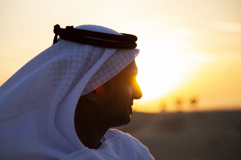 Close-up of man in traditional clothing against sky during sunset