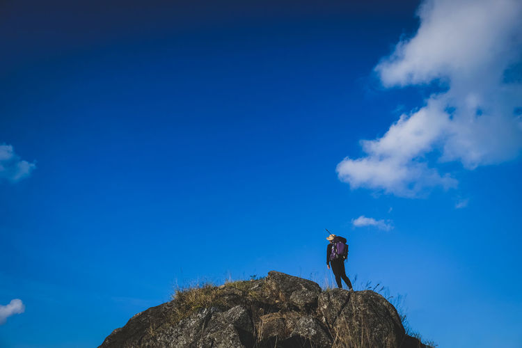 Low angle view of person standing on rock against blue sky