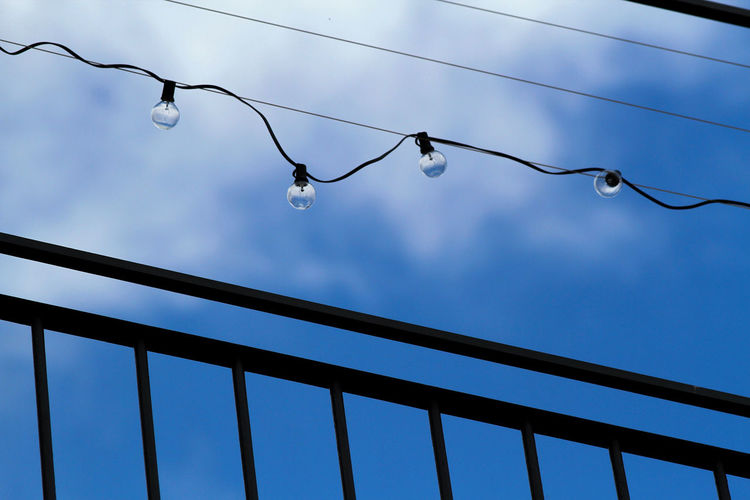 Low angle view of water drops on cable against sky