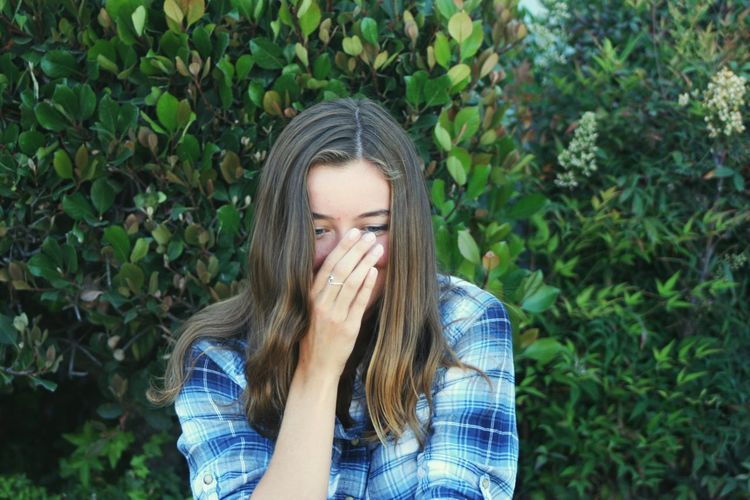 Shy teenage girl covering mouth with hand while standing against plants at park