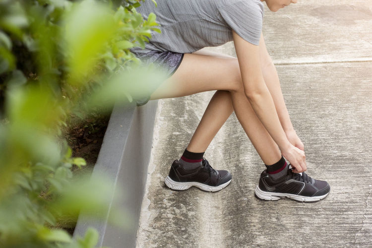 Low section of woman sitting on retaining wall in park