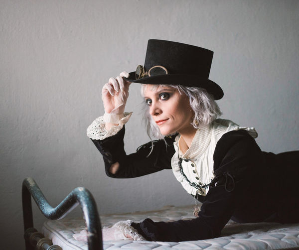 Woman wearing costume while lying on bed at home
