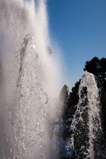 Waves splashing on water against sky
