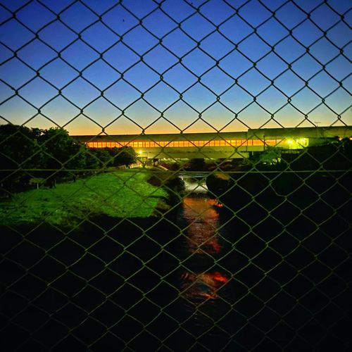 Chainlink fence on field against sky during sunset