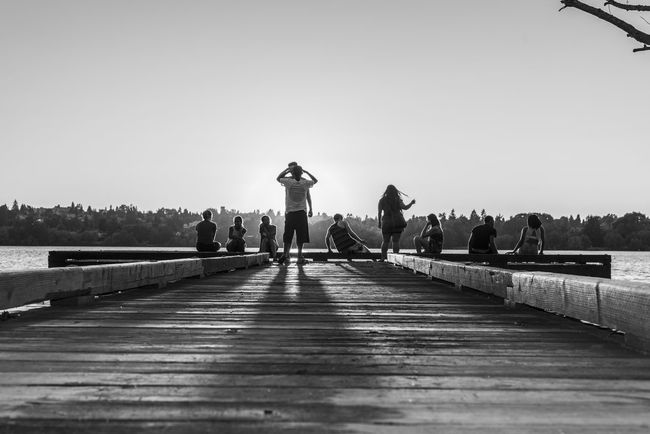 Black and white young people hanging out on a lake pier at sunset Black And White Bridge - Man Made Structure Clear Sky Day Friends Full Length Group Leisure Activity Lifestyles Men Nature Outdoor Recreation Outdoors People Real People River Sky Summer The Way Forward Tree Water Women Youth