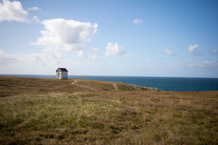 Hut on cliff by sea against sky