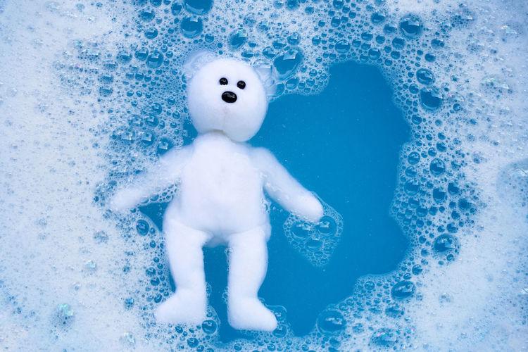 Teddy bear in soap sud