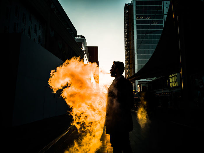 Double Exposure Of Man Standing By Fire With City In Background