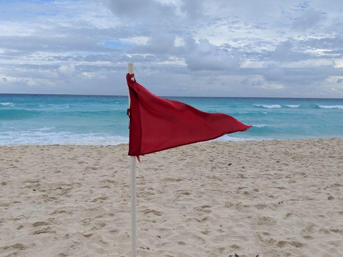 Red flag on beach against sky