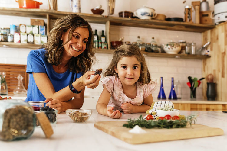 Smiling mother feeding food to daughter in kitchen at home