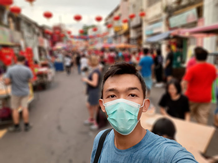 Portrait of young man with protective mask  in front of a street market with chinese lanterns