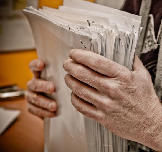 Close-Up Of Man Holding Papers