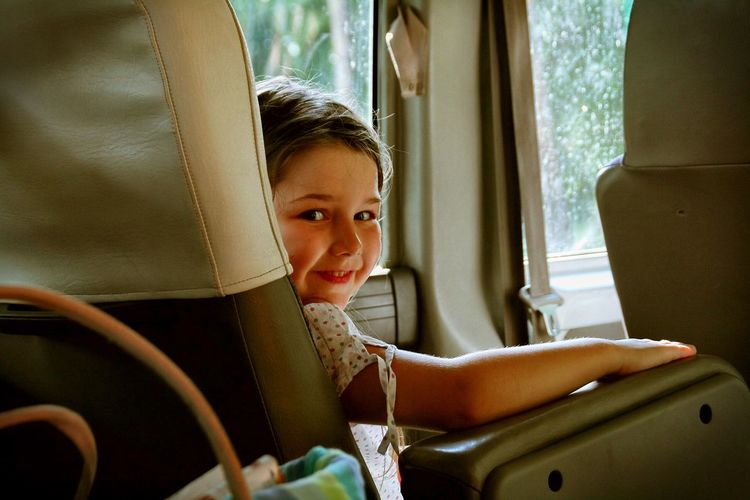 Cute Girl Sitting In The Interior Of A Vehicle
