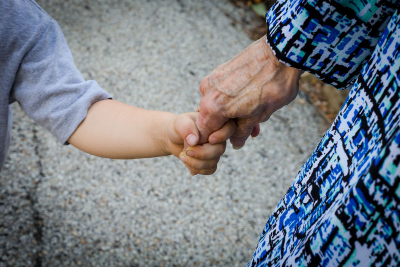 Midsection of grandmother holding grandson hand while standing on road