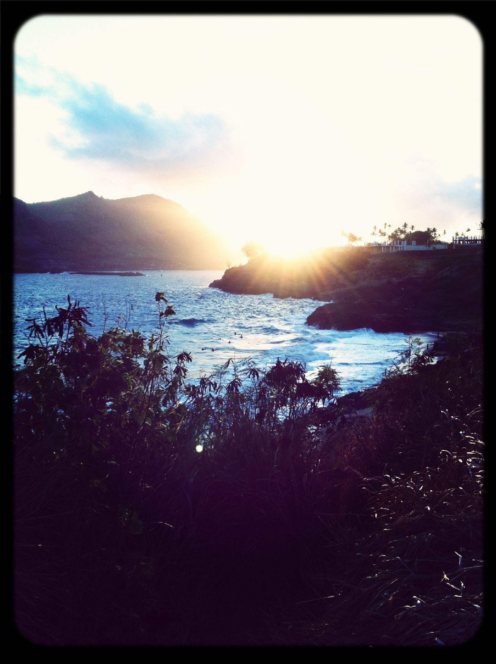 transfer print, water, sun, sea, sky, scenics, tranquil scene, beauty in nature, tranquility, auto post production filter, sunset, nature, horizon over water, sunlight, beach, sunbeam, idyllic, shore, mountain, reflection