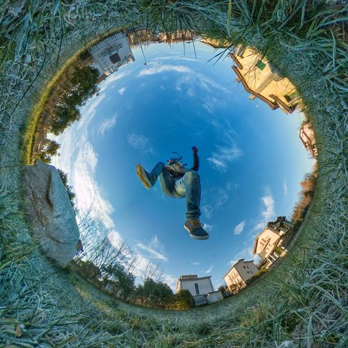 Little planet format of man jumping against sky