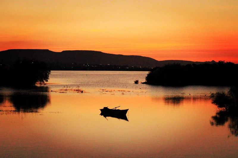 Silhouette ducks on lake against sky during sunset