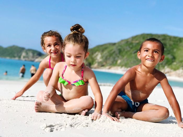 Cute siblings playing at beach during sunny day