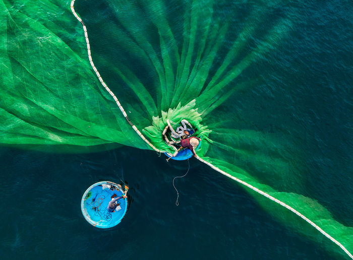 Drone shot of fisherman putting fishing net in sea