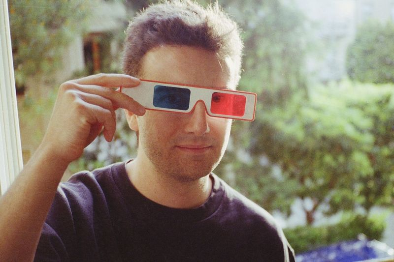 Portrait of handsome man looking through 3-d glasses