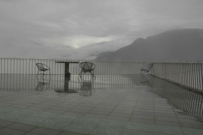 Empty Chairs And Table On Pier Against Mountains