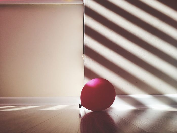 Close-up of magenta balloon on table at home