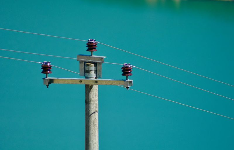 Low angle view of power pole against blue sky