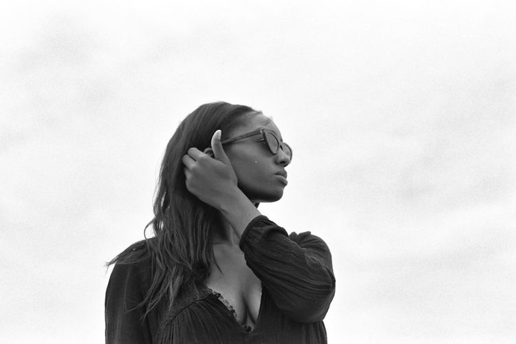 Portrait of young woman looking away against sky