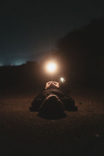 Man lying down on illuminated street against sky at night
