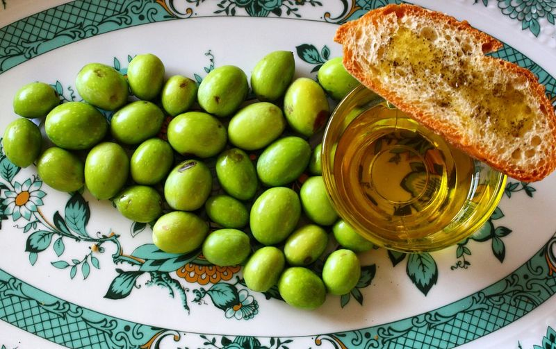 Fresh olives and olive oil with bread of a plate